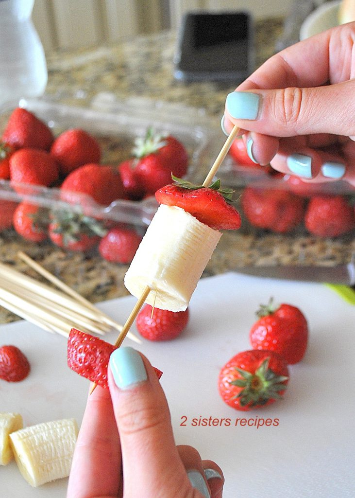 A photo of alternating fruit pieces onto skewer. by 2sistersrecipes.com