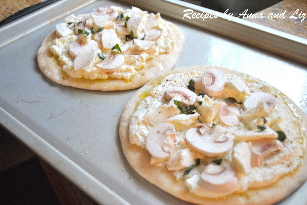 Two pita breads on a baking sheet ready to bake. by 2sistersrecipes.com