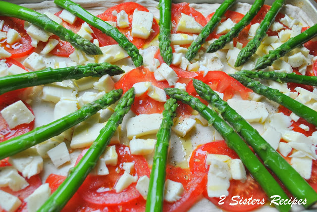 A closeup photo of the AsparagusTomato and Cheese Pizza by 2sistersrecipes.com