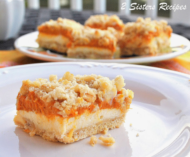 Photo of the pumpkin cheesecake bars on a plate. by 2sistersrecipes.com