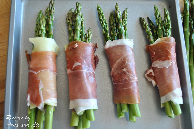 Thin asparagus wrapped in bundles on a baking sheet. by 2sistersrecipes.com