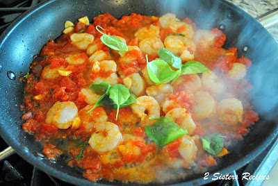 Skillet on the stove filled with tomatoes, shrimp and basil. by 2sistersrecipes.com