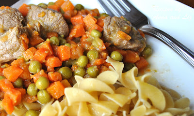 a white plate with noodles, peas, carrots and chunks of veal. by 2sistersrecipes.com