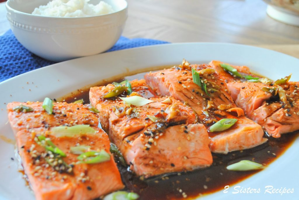 A platter with cooked salmon with teriyaki sauce. by 2sistersrecipes.com