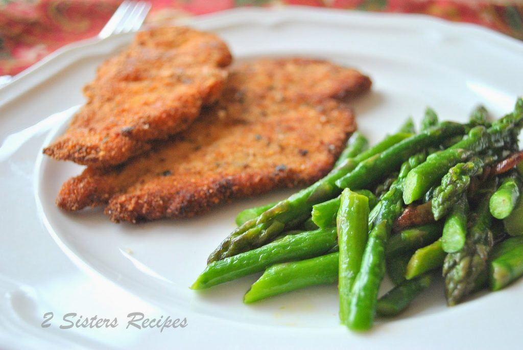 A white dinner plate with chicken cutlets and garlicky asparagus on the side. by 2sistersrecipes.com