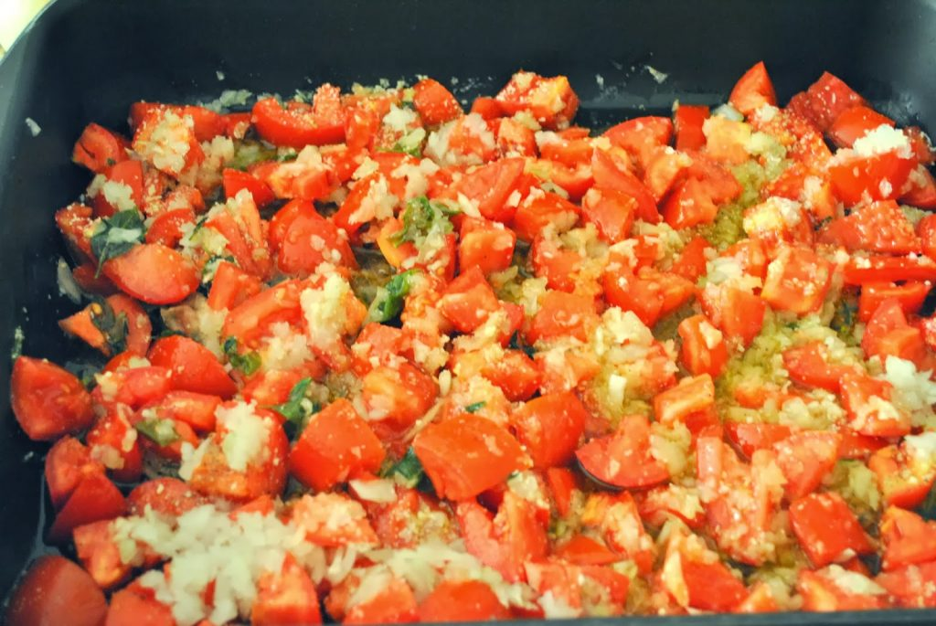 Roasting pan filled with chopped tomatoes and onions by 2sistersrecipes.com