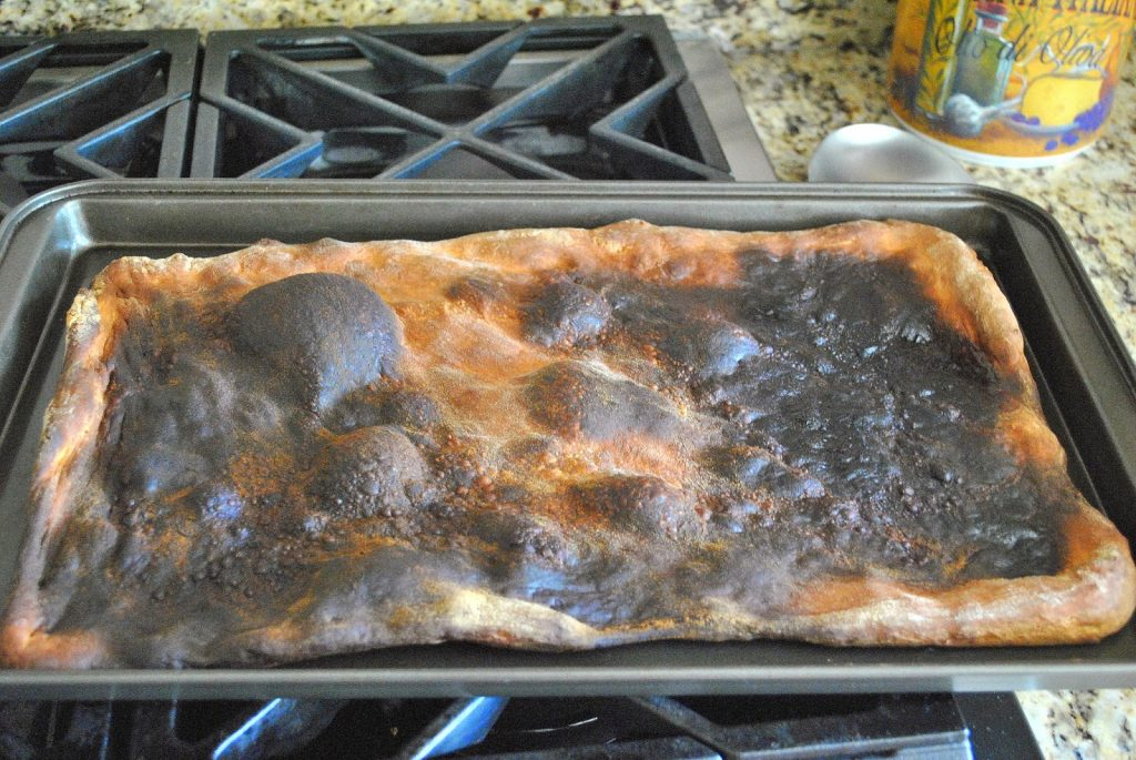 A photo of a pizza dough burnt when over baked/ by 2sistersrecipes.com
