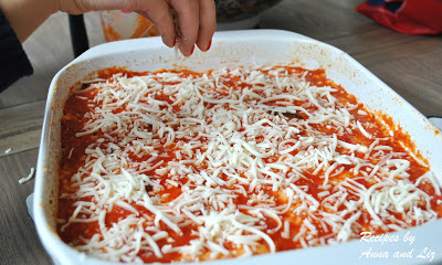 Final sprinkle of shredded mozzarella on top a layer of sauce. by 2sistersrecipes.com