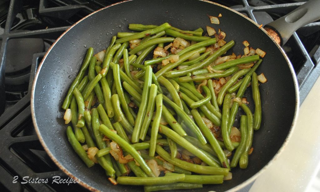 Green beans are cooking in a large skillet on stovetop. by 2sistersrecipes.com