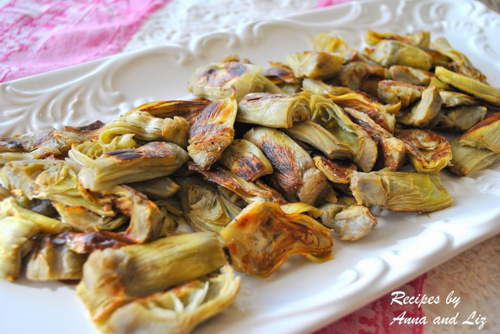 a white platter filled with roasted artichoke hearts. by 2sistersrecipes.com