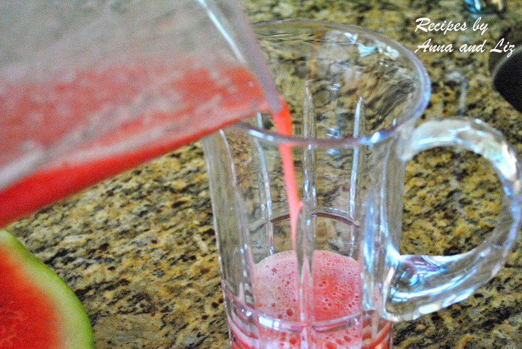 watermelon juice is poured into a glass pitcher. by 2sistersrecipes.com