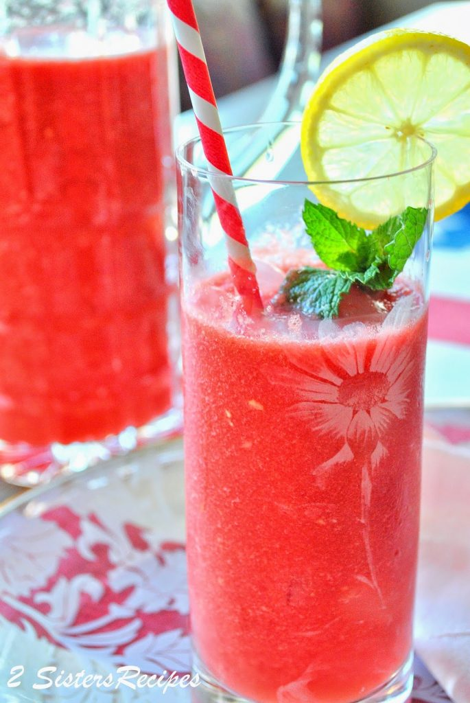 A photo of the watermelon drink in a tall glass, with a slice of lemon and mint. by 2sistersrecipes.com