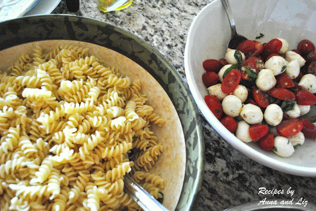 A photo of fusilli pasta in one bowl and cherry tomatoes and mini mozzarella balls in the other bowl.  by 2sistersrecipes.com