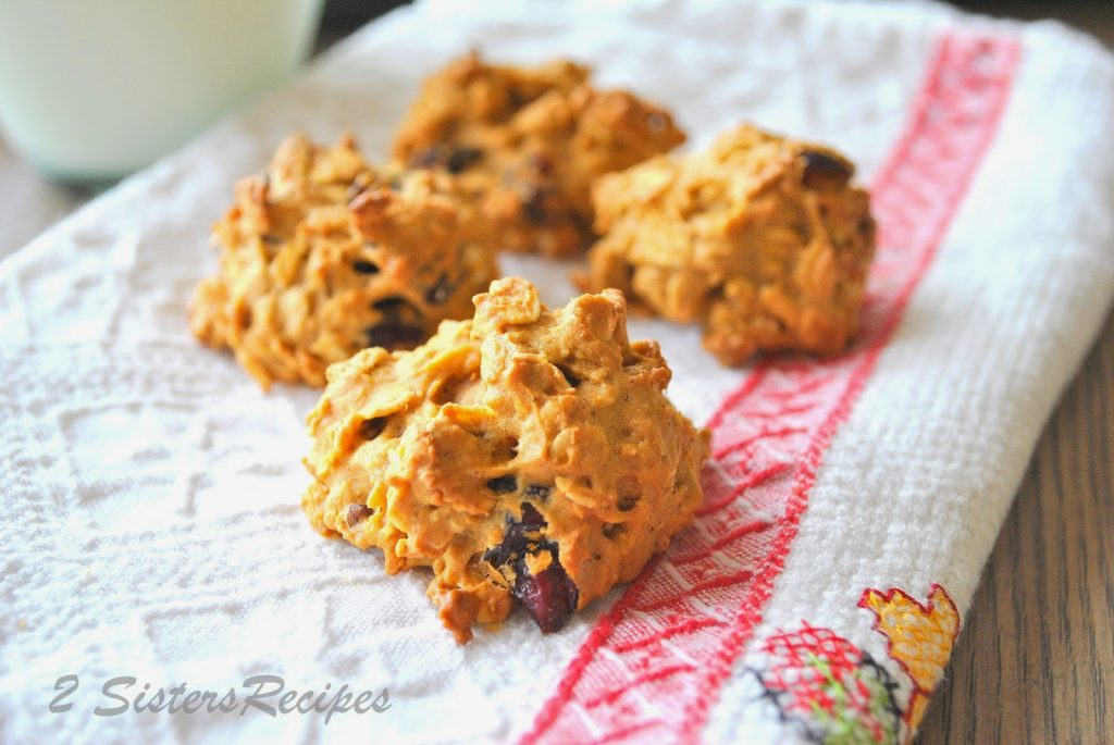 Four pumpkin cookies on a kitchen towel. by 2sistersrecipes.com