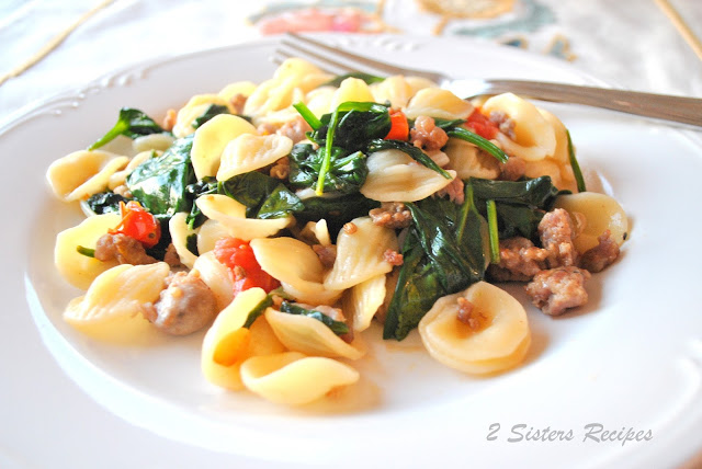 A white plate with orecchiette pasta, crumbled sausages and spinach. by 2sistersrecipes.com