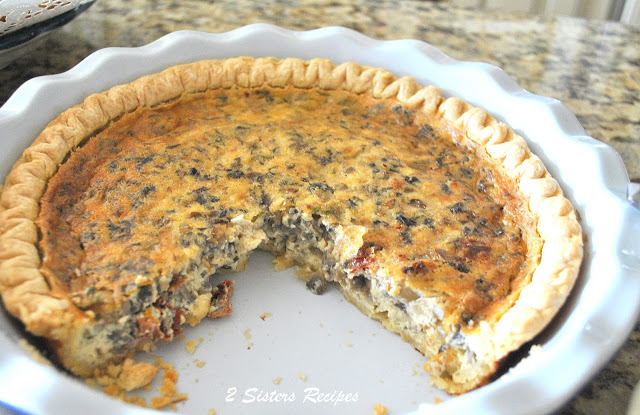 A baked quiche sliced in baking dish by 2sistersrecipes.com