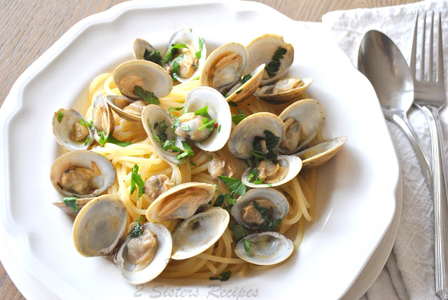 A white dish with spaghetti and Little Neck Clams on top. by 2sistersrecipes.com