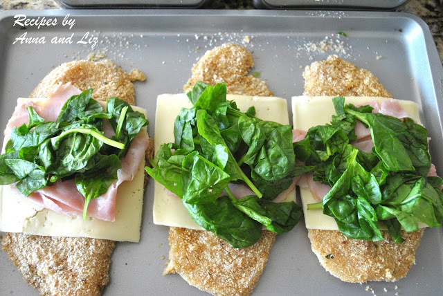 Chicken cutlets prepared on a baking sheet with spinach on top, ready to be rolled .by 2sistersrecipes.com