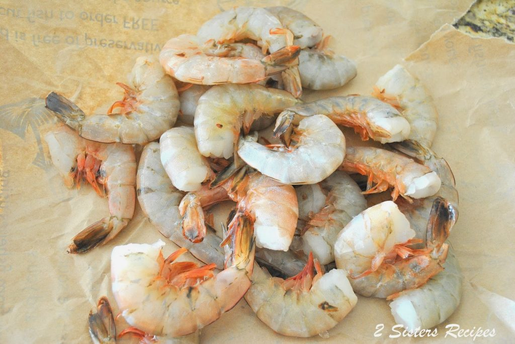 raw shrimps on brown paper by 2sistersrecipes.com