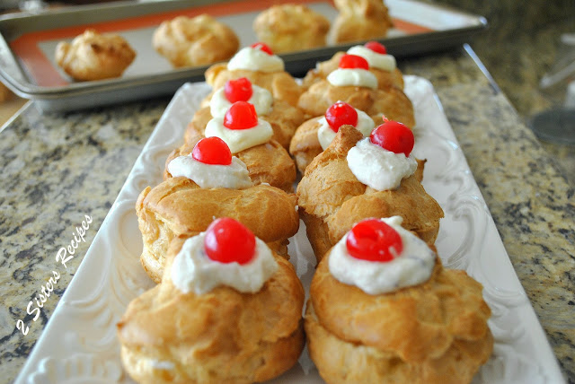 A white platter filled with cream puffs and each topped with a cherry. by 2sistersrecipes.com