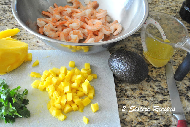 Chopped mango on a cutting board with shrimp in a mixing bowl. by 2sistersrecipes.com