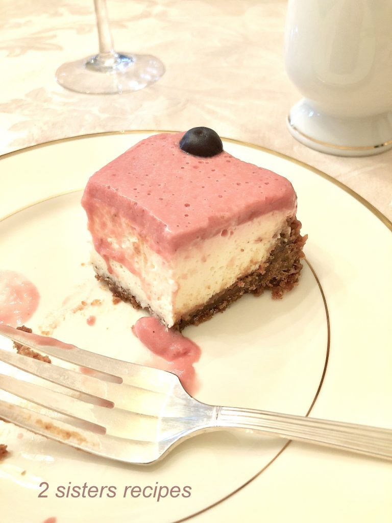 A slice of the Cheesecake on a serving plate. by 2sistersrecipes.com