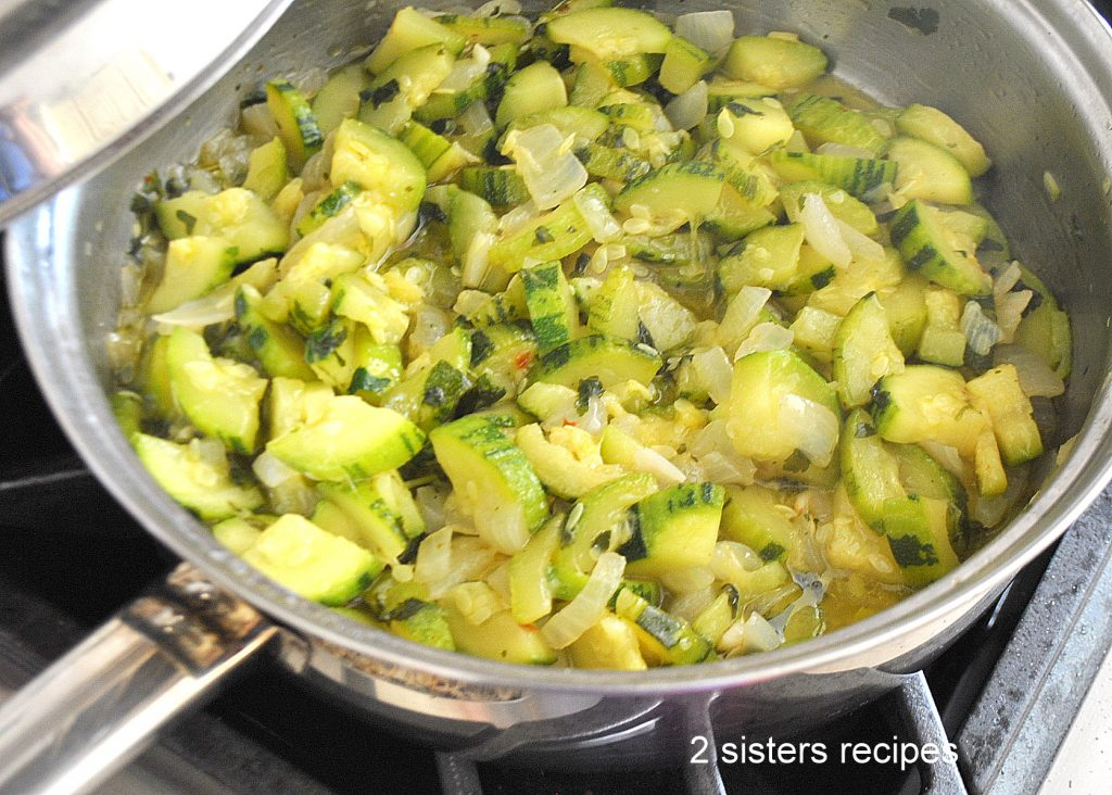 Zucchini cooking in a large skillet with onions by 2sistersrecipes.com