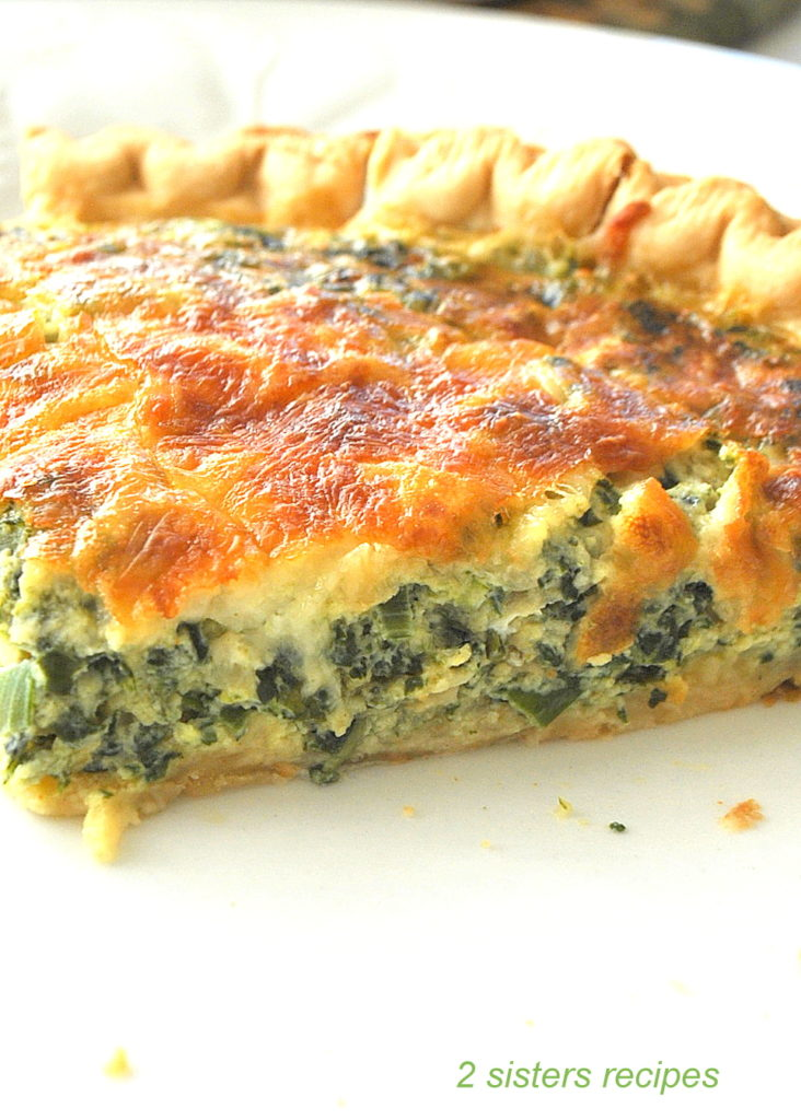A slice of a spinach and kale Quiche on a white plate. by 2sistersrecipes.com