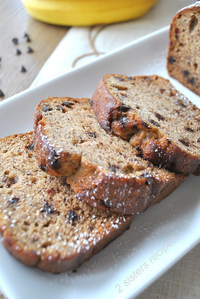 Sliced banana bread on a white serving plate by 2sistersrecipes.com