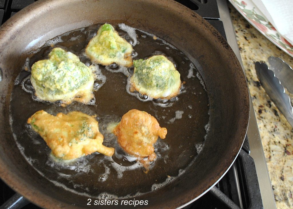A skillet filled with broccoli frying. by 2sistersrecipes.com