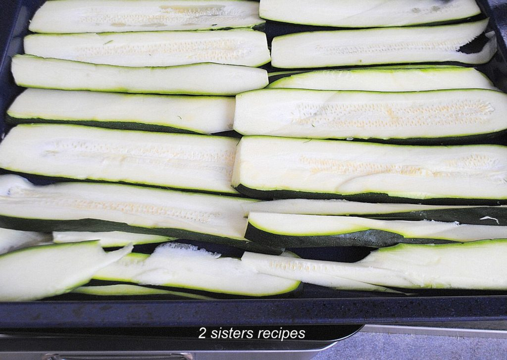 Sliced Zucchini in a large baking pan by 2sistersrecipes.com