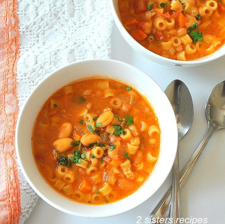 A white bowl of pasta fagioli soup. by 2sistersrecipes.com