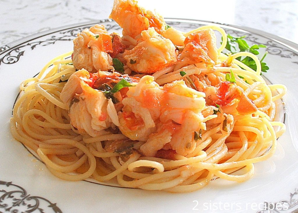A plate with spaghetti and chunks of lobster on top. 2sistersrecipes.com