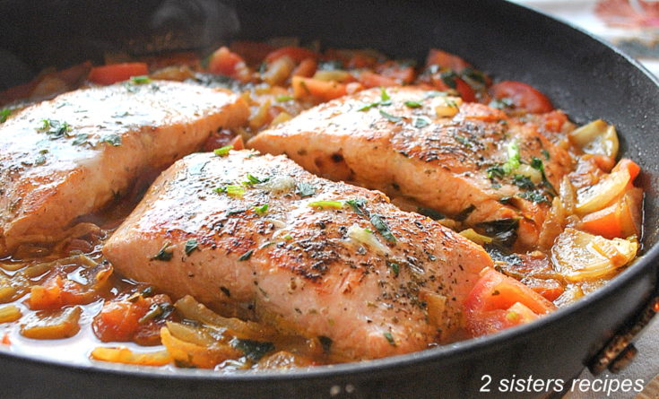 Pan seared salmon cooked in skillet with the tomato sauce. by 2sistersrecipes.com