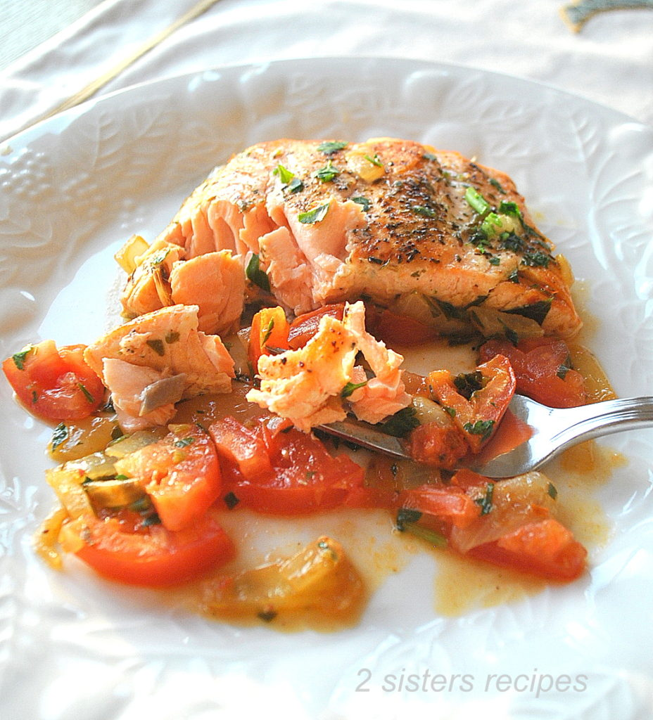A forkful of cooked salmon on a white plate. by 2sistersrecipes.com