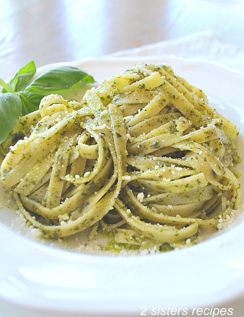 A plate filled Fettuccine with spinach pesto sauce. by 2sistersrecipes.com