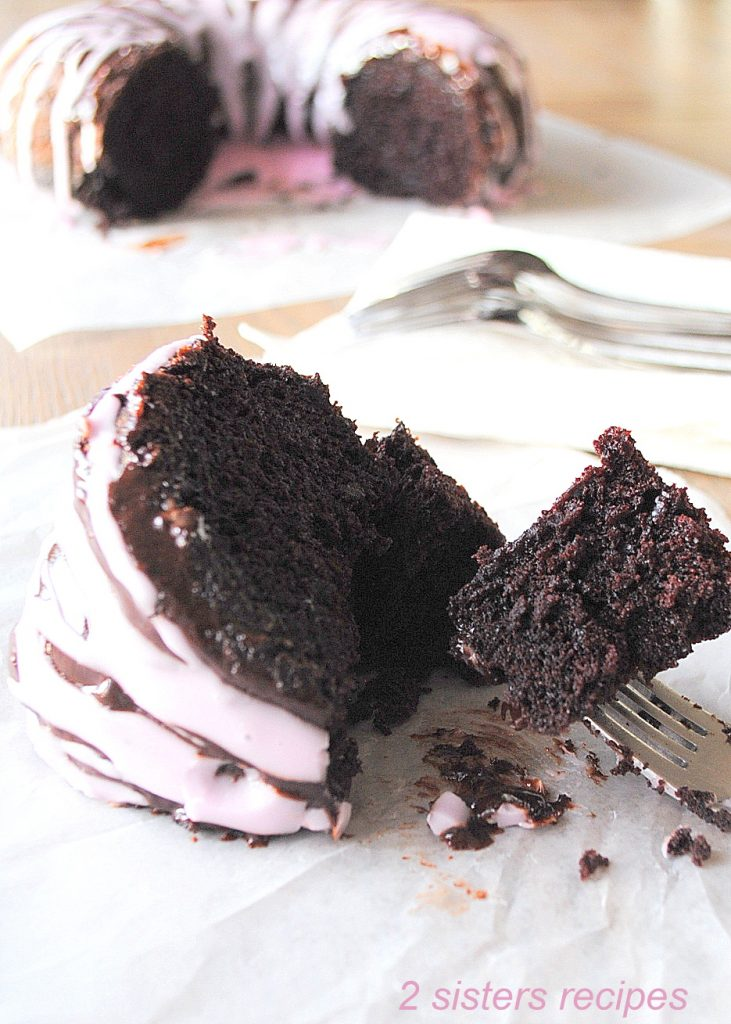 A slice of cake on wax paper with a fork cut into the slice. by 2sistersrecipes.com