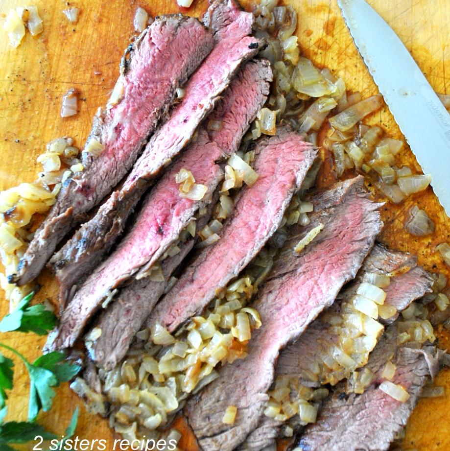 sliced steak on a cutting board. by 2sistersrecipes.com
