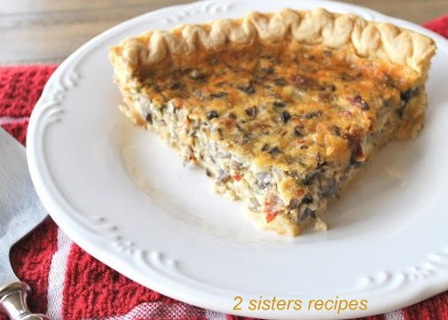 A piece of sliced Quiche on a white plate by 2sistersrecipes.com