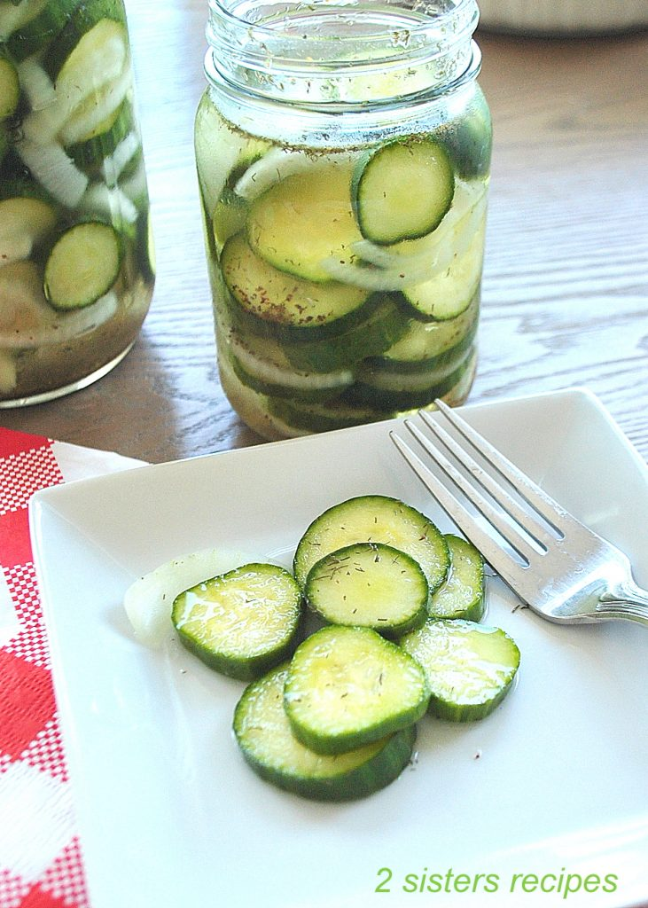 A few pickles on a white plate with a fork. by 2sistersrecipes.com