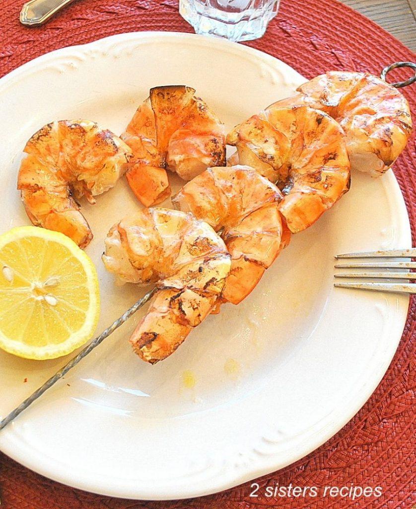 A white plate with a Jumbo Shrimp Kabob and a lemon. by 2sistersrecipes.com