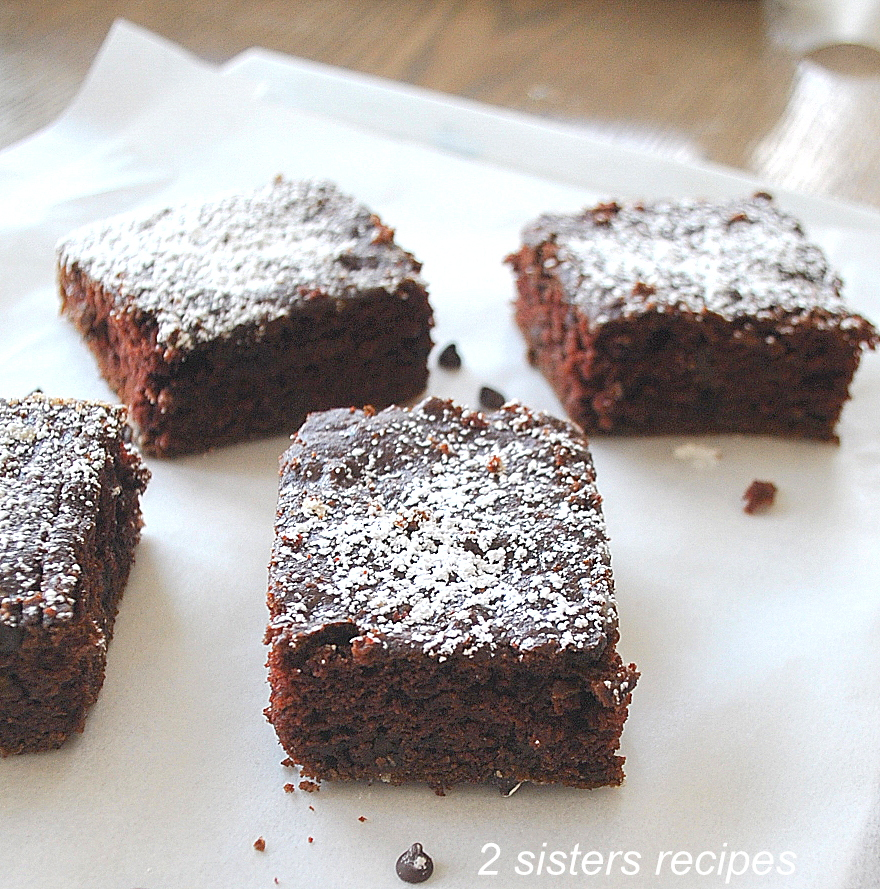 Four brownies on sheet of wax paper. by 2sistersrecipes.com