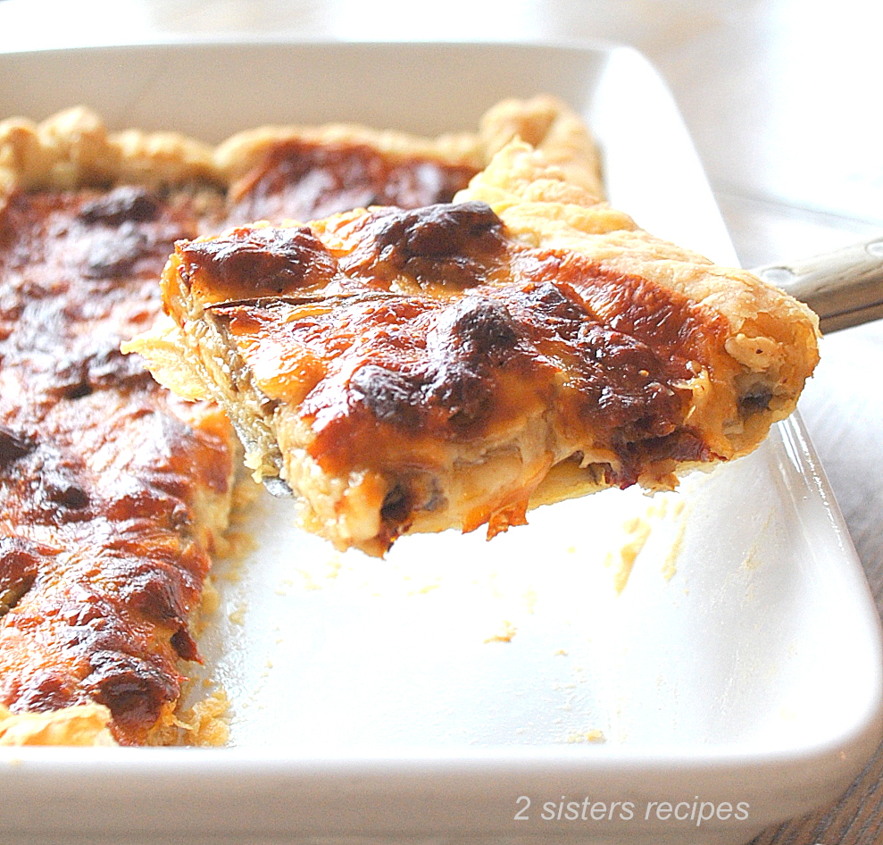 A slice of tart held in a spatula. by 2sistersrecipes.com
