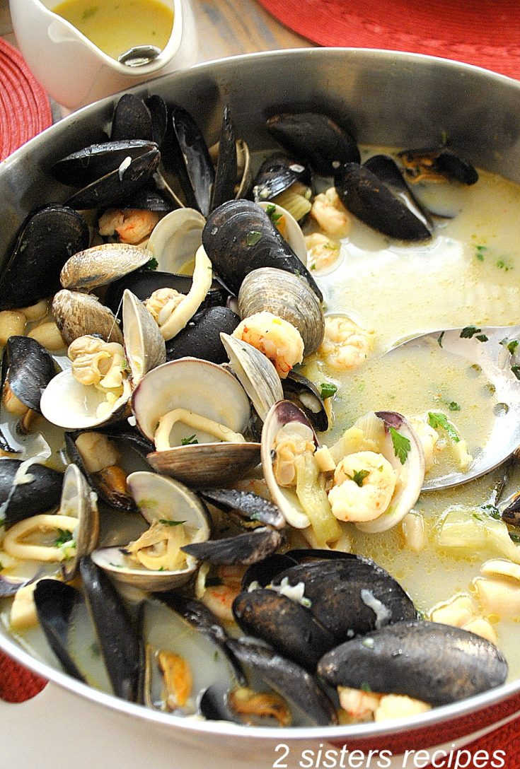 Mixed seafood in a wide pot on the table. by 2sistersrecipes.com