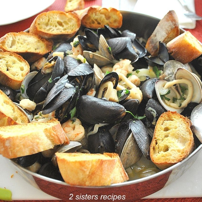 a large pot with mixed seafood and slice toasted bread around the stew. by 2sistersrecipes.com