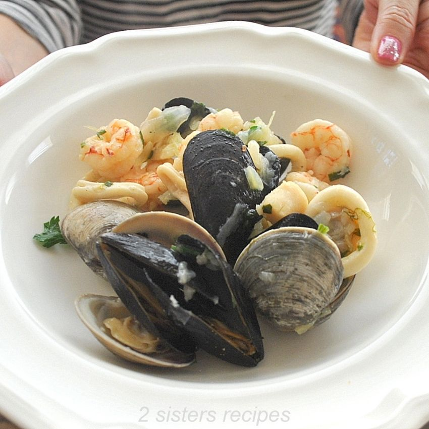 A plate filled with mixed seafood stew. by 2sistersrecipes.com