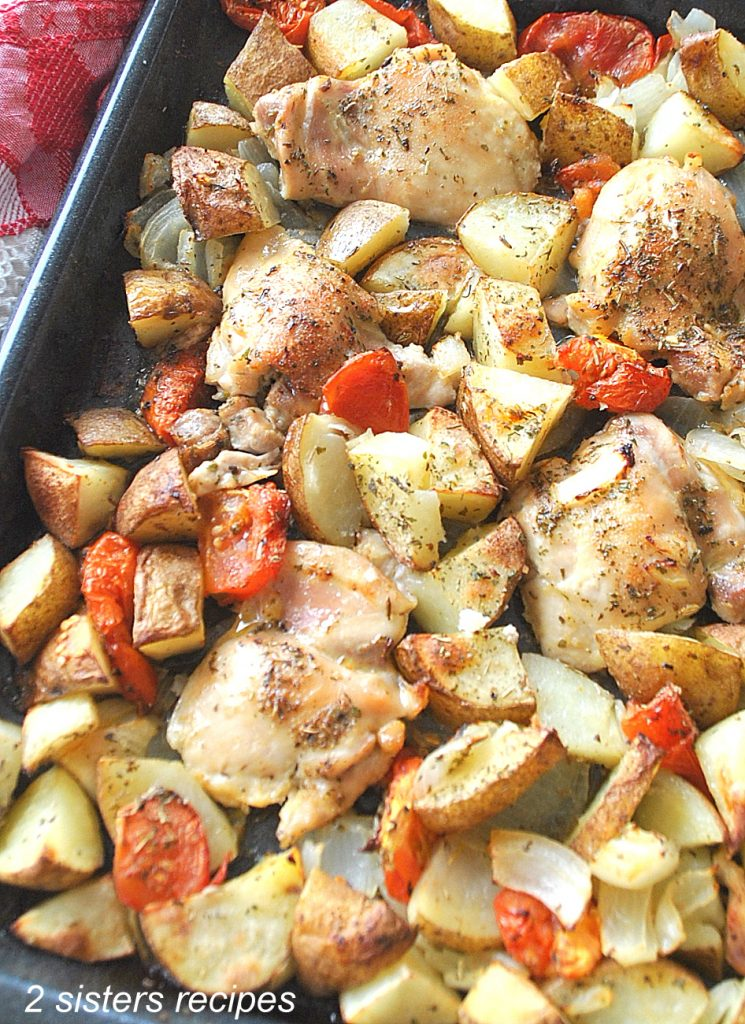 Full baking pan with chicken thighs and veggies. by 2sistersrecipes.com